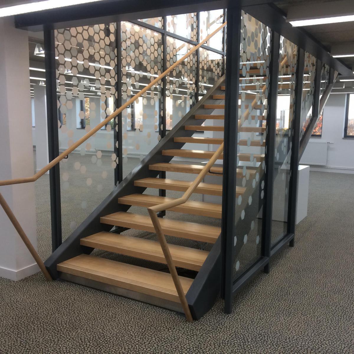 Escalier intérieur en acier peint et marche en bois. Des panneaux en verre trempé assurent la fonction de garde-corps<br>
